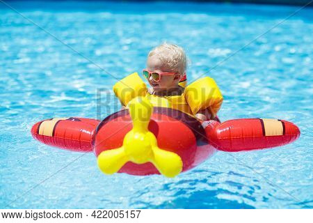 Baby In Swimming Pool Floating On Toy Ring. Kids Swim. Colorful Float For Young Kids. Little Child H