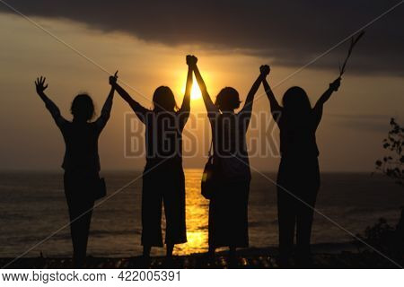 Group Of People Silhouette At Sunset. Young Women Holding Hands, Hand Raised Against Golden Sun Ligh