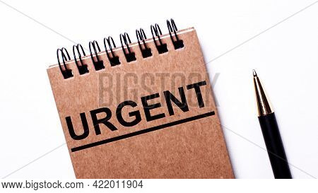 On A Light Background, A Black Pen And A Brown Notebook On Black Springs With The Inscription Urgent
