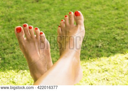 Red Nail Polish With A Green Grass Background