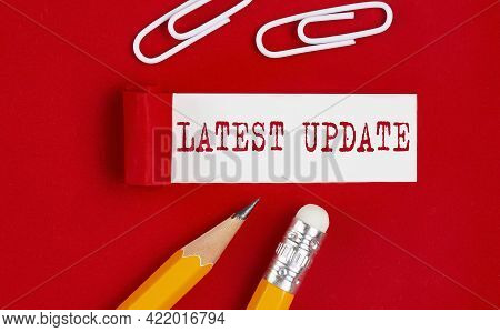 Latest Update Message Written Under Torn Red Paper With Pencils And Clips, Business