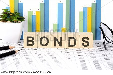 Bonds Word Written On The Wood Block With Chart, Glasses And Pencils