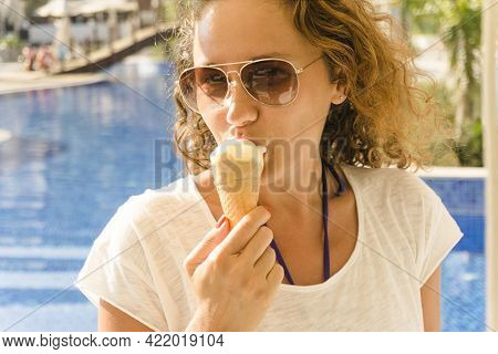 Young Woman Eating Ice Cream On The Poolside