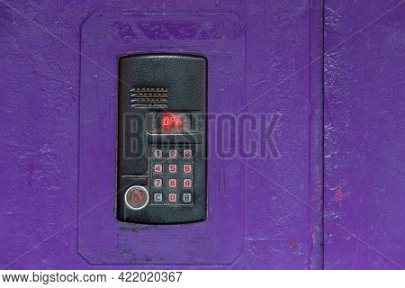 An Intercom On Purple Painted Red Steel Surface With A Keypad, Digital Display And Rfid Sensor For C