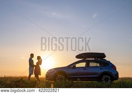 Happy Couple Standing Near Their Car At Sunset. Young Man And Woman Enjoying Time Together Travellin