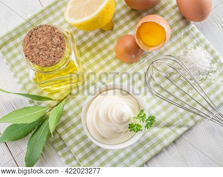 Bowl with mayonnaise sauce in the centre and mayonnaise ingredients around it on wooden table. Top view.
