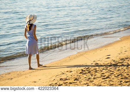 Young Woman In Straw Hat And A Dress Walking Alone On Empty Sand Beach At Sea Shore. Lonely Tourist