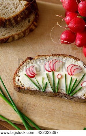 Bread Slice With Butter Radish And Chives On A Wooden Table