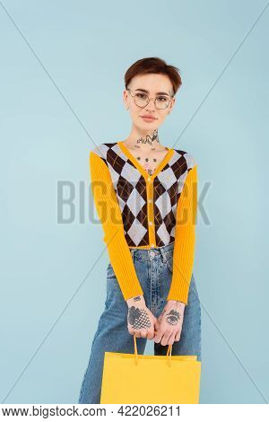 Tattooed Young Woman In Glasses And Cardigan Holding Shopping Bag Isolated On Blue.