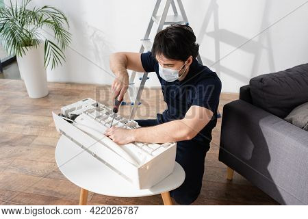 Handyman In Medical Mask Holding Screwdriver While Fixing Broken Air Conditioner.