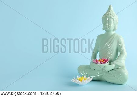 Beautiful Ceramic Buddha Sculpture With Flowers On Light Blue Background. Space For Text