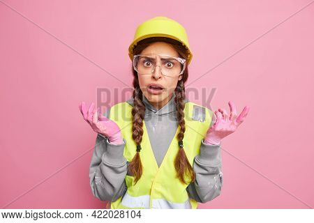 Indignant Displeased Woman Builder Industrial Worker Shrugs Shoulders Feels Puzzled Spreads Hands Si