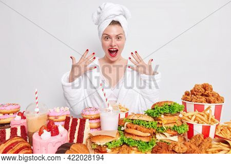 Positive Housewife Dressed In White Bath Robe And Wrapped Towel On Head Shows Red Manicure Eats Junk