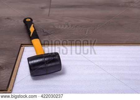 Rubber Hammer On Laminate Floor With Copy Space For Text. Carpenter Tool For Laying Laminate In The