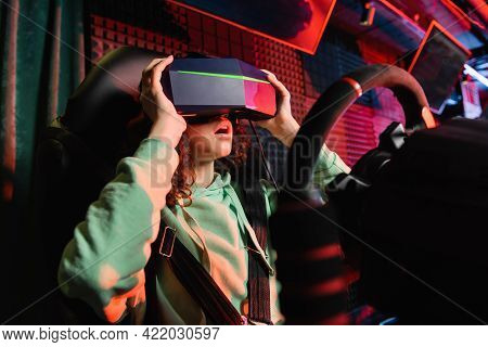 Astonished African American Girl Touching Vr Headset While Playing On Car Racing Simulator.