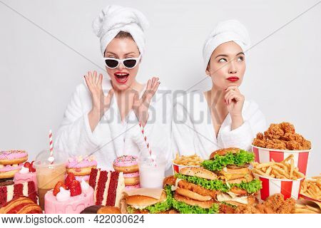 Joyful Woman Addicted To Junk Food Wears Sunglasses Raises Palms Feels Very Glad Other Female Model