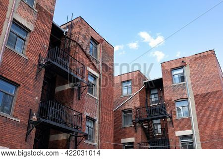 Urban Landscape Rear View Of Old Brick Apartment Buildings With Black Metal Fire Escapes Against A B