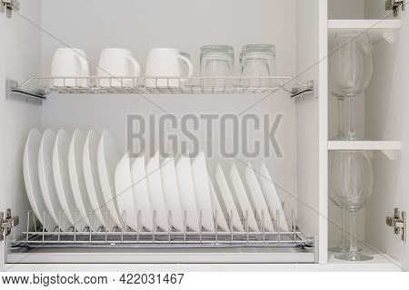 Set Of Clean White Dishes, Mugs And Different Glasses And Other Crockery In Opened White Kitchen Cup