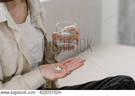 Cropped View Of Young Unhealthy Woman Hold Glass Of Water And Treatment Pills In Her Hand. Female Ta