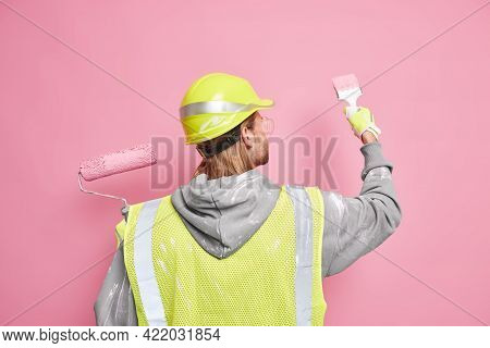 Busy Building Contractor Stands Back To Camera Paints Wall With Brush Dressed In Working Uniform And