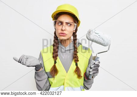 Puzzled Hesitant Woman Builder Or Decorator Wears Uniform Protective Hardhat And Transparent Glasses