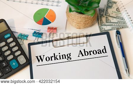 Paper With Working Abroad On The Office Table, Calculator And Money