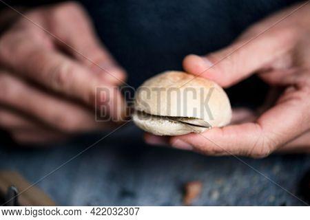 closeup of a young caucasian man cutting a mini bread bun to prepare a mini sandwich, sitting at a gray wooden table