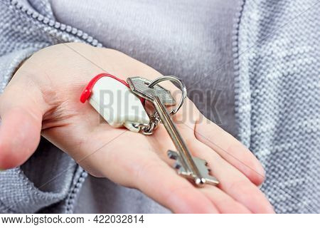 Woman Hands Holding The Keychain With The Keys And Small House Key Ring Close Up. Apartment Renter,