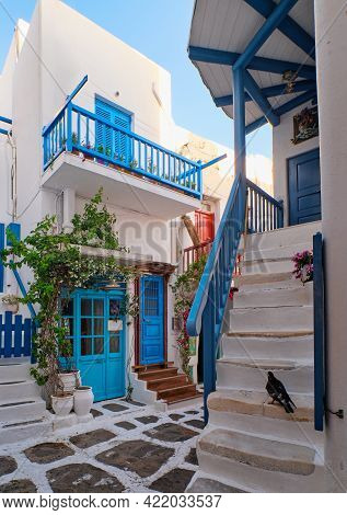 Traditional Narrow Cobbled Streets, Beautiful Alleyways Of Greek Island Towns. White Houses, Flower
