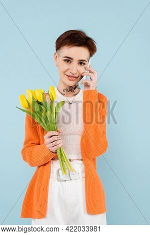 Young Tattooed Woman In Orange Cardigan Holding Yellow Tulips While Talking On Smartphone Isolated O