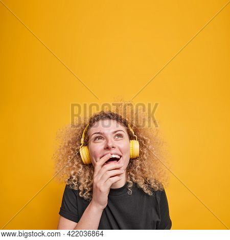 Vertical Shot Of Overjoyed Curly Haired Woman Looks Above Gladfully Keeps Hand On Mouth Wears Stereo