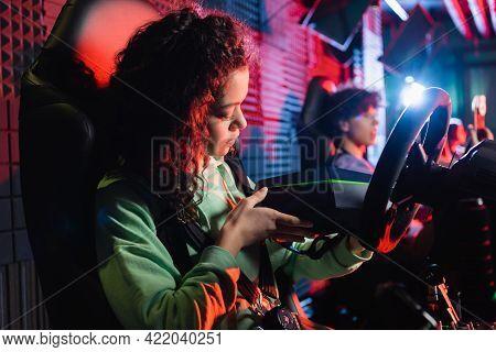 African American Girl Holding Vr Headset Near Blurred Friend In Car Simulators.