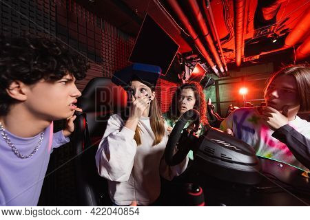 Shocked Girl On Racing Simulator Covering Mouth With Hand Near Interracial Friends.