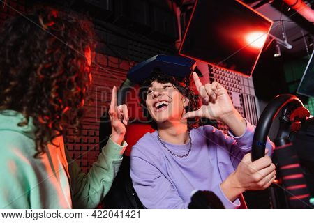 Excited Interracial Friends Showing Idea Gesture Near Car Racing Simulator.
