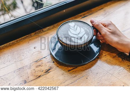 Cropped Shot View Of Someone Hand Touching A Cup Of Goth Latte Or Charcoal Latte On Wooden Table. Th