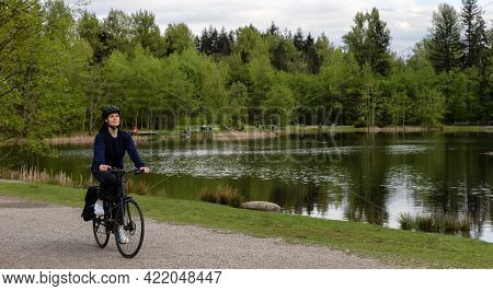 Adult Caucasian Woman Riding A Bicycle On A Path By A Lake In A Modern City Park. Spring Evening. Ta