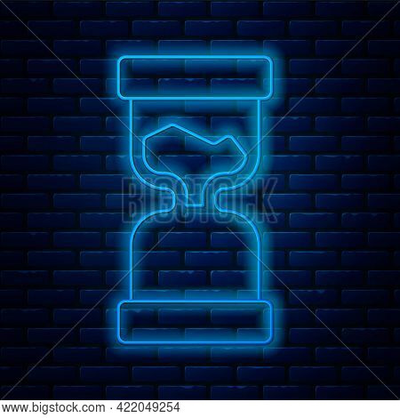 Glowing Neon Line Old Hourglass With Flowing Sand Icon Isolated On Brick Wall Background. Sand Clock