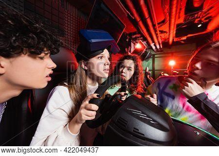 Teenage Girl Gaming On Car Racing Simulator Near Worried Multiethnic Friends.