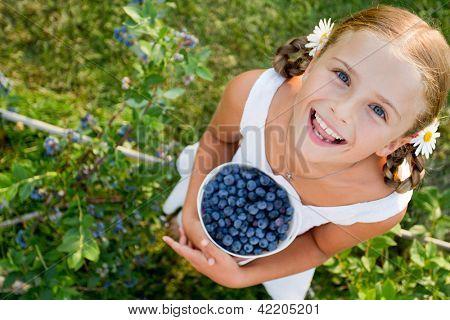 Blueberries, summer, child - Lovely girl with fresh blueberries in the garden