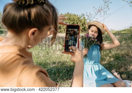 Back View Of Young Woman Holding Cell Phone And Making Photo Of Her Girl Friend. Two Girlfriends Tak