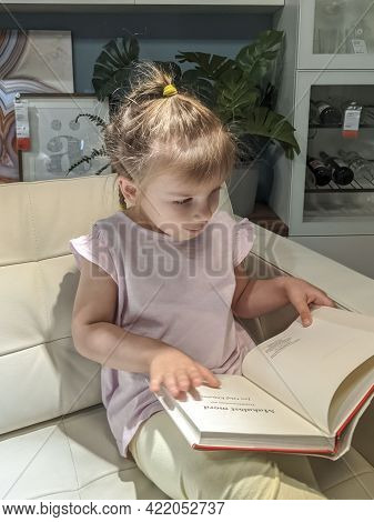 05.23.2021 Ikea, Moscow, Russia. Baby Examines A Book In The Store On The Sofa