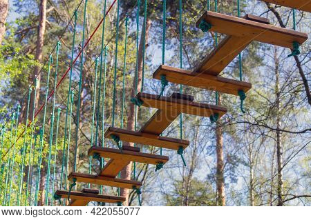 Wooden Movable Elements Fixed With Ropes On A Rope (climbing) Camp In The Trees. Red Safety Rope In