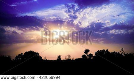 Purple With Orange Sunset In Overcast Blue Sky With Sun Rays Light. Amazing View Of Sunset Seascape