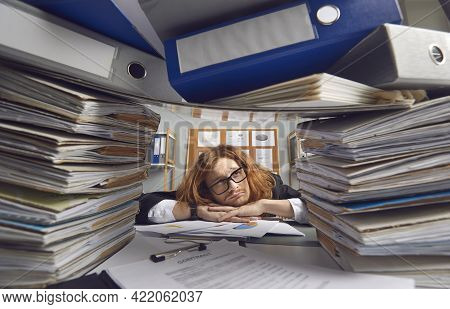 Tired Office Worker Sitting At Desk And Looking Apathetically At Piles Of Paperwork