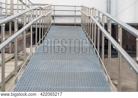 Metal Ramp With Railing For Sedentary People. The Path Is Up With A Right Turn. Front View.