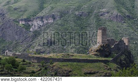 An Ancient Fortress On A Rock Against The Backdrop Of A Mountain Range Overgrown With Green Vegetati