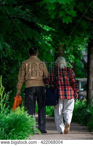 Two Elderly People Walking On The Street. Real People. View From Behind
