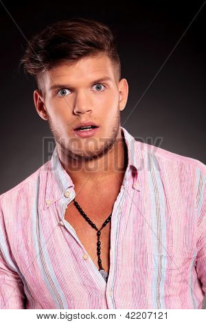 portrait of a young casual man posing surprised while looking at the camera, on dark background