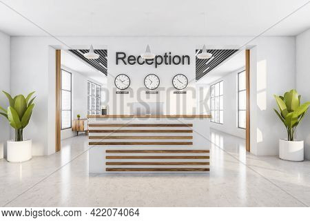Light Reception Room Interior With Computer, Clocks On The Wall. Reception Entrance With Office Desk