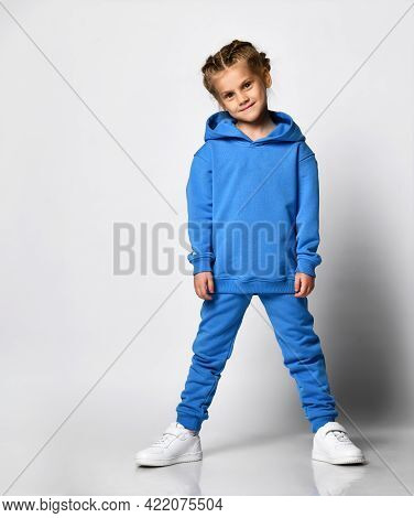 Smiling Cute Girl In A Blue Tracksuit With A Hood And Pants, White Sneakers, Isolated On White. Port